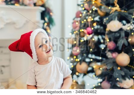 Adorable Cute Child Boy Having Fun Playing At Home In Red Santa Claus Hat And Festive Christmas Tree