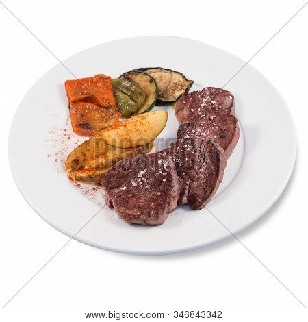 A Beef Sirloin With Baked Potatoes And Some Vegetables Dish On A White Background