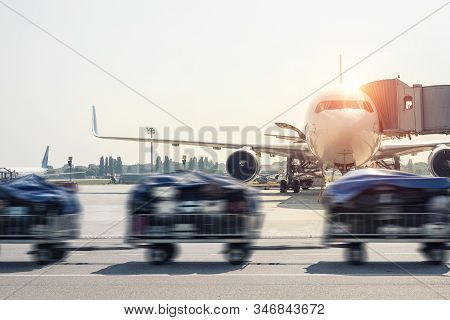 Luggage Motion Blurred Trolley Cart Going Fast Delivering Passenger Baggage To Modern Plane On Taxiw