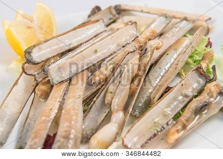 Detail Of A Dish Of Grilled Razor Clams With Lemon And Parsley