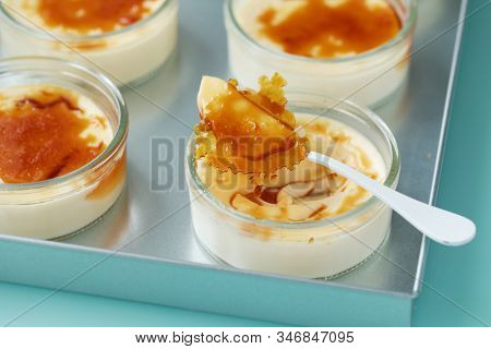 Closeup view of a portion of creme brulee dessert in jars topped with caramelized sugar on tray