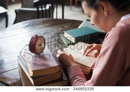 Too Little Time. An Alarm Clock Stands On A Stack Of Books, Next To Glasses, On A Table In An Old Li