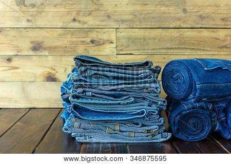 Jeans Stacked On Wooden Floor. Blank Background For Design And Text Input.