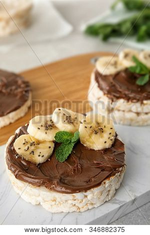 Puffed Rice Cakes With Chocolate Spread, Banana And Mint On Board, Closeup