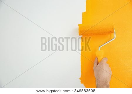 Man Painting White Wall With Yellow Dye, Closeup. Interior Renovation