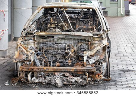 A Burnt Car Is Standing On The Sidewalk Of A City Street, Front View Of A Burnt Out Passenger Compar