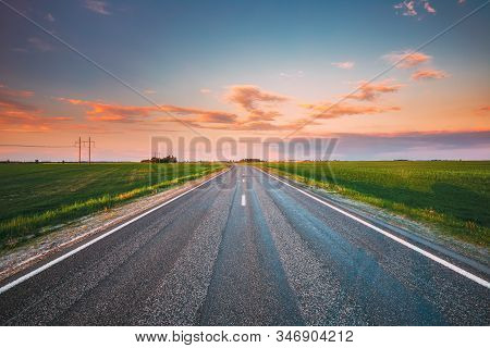 Asphalt Country Open Road Through Spring Fields And Meadows In Sunny Evening. Landscape In Early Sum