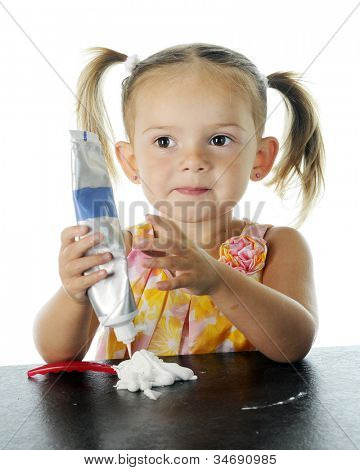 Closeup view of a beautiful preschooler looking pleased with her efforts to load her own toothbrush with toothpaste.  On a white background.