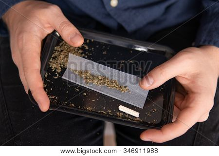 Man Rolling A Marijuana Joint. Man Preparing And Rolling Marijuana Cannabis Joint. Drugs Narcotic Co