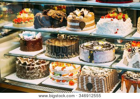 Various Different Types Of Sweet Cakes In Pastry Shop Glass Display. Good Assortment Of Confectioner