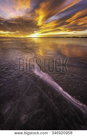 Colorful Sunrise On The Frozen Lake With Ice Cracks Glowing