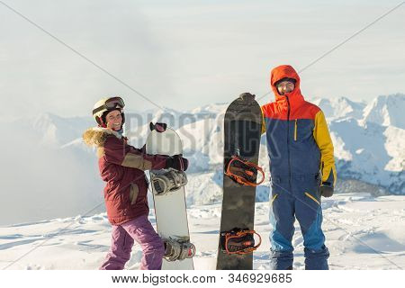 Couple Snowboarding Freeriders Man And A Woman Stand On The Background Of Snowy Mountains