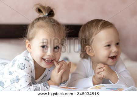 Lovely Children - Brother And Sister, Reading A Book, On The Bed. Close Up Of Children In Bed Readin