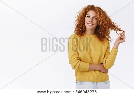 Creative, Stylish Pretty Redhead Curly Girl In Yellow Sweater, Rolling Hair Strand On Fingers And Sm