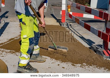 Worker With Warning Trousers And Working Shoes Is Scrubbing With A Street Broom In His Hand On The S