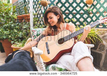 Beautiful Woman Playing Guitar Outdoors.