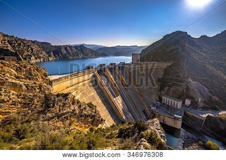View Of Hydroelectric Dam At Embalse De Santa Ana Reservoir Lake In Sierras Exteriores, Spanish Pyre