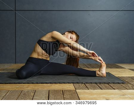 Beautiful Redhead Woman Stretching Her Leg On The Floor Sitting On A Mat.