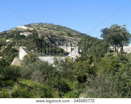 Green Hill In Front Of The Blue Sky And Germasogeia Dam, Cyprus Overflowing After The Heavy Winter R