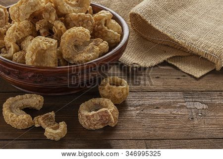 Foreground Of Some Pork Rinds On A Brown Dish Over A Wooden Table And A Burlap Fabric