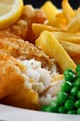 Close up of fish and chips with peas and a slice of lemon. A traditional British Seaside Dish poster
