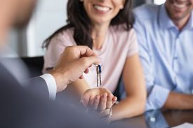 Close up of man hand giving house keys to woman. Smiling mature woman receiving new house keys from real estate agent. Man delivering keys to client for new home. Real estate agent giving keys.