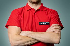 Security Service Guard In Red Uniform Standing On Gray Background With Arms Crossed