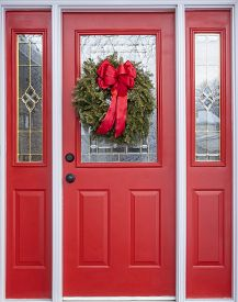 Red House Door Decorated With A Real Pine Christmas Wreath And A Big Red Satin Bow