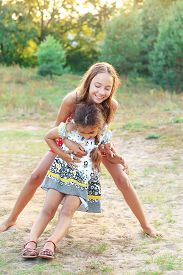 Two Happy Little Girl Embracing And Playing At Sunny Summer Day