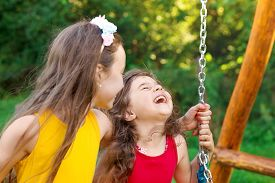 Two Happy Beautiful Girls Sitting On Swing And Smiling At Warm  Summer Day