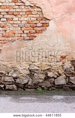 Wall With Chipped Plaster, Stone Foundation And Asphalt