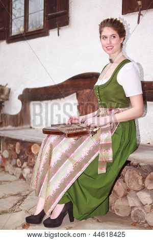 Young Bavarian girl playing the zither on a bank