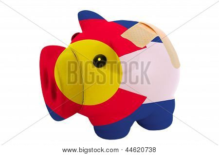 Closed Piggy Rich Bank With Bandage In Colors Flag Of American State Of Colorado