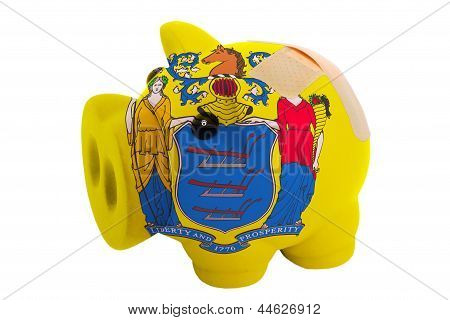 Closed Piggy Rich Bank With Bandage In Colors Flag Of American State Of New Jersey
