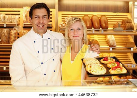 Baker And Shopkeeper In Bakery With Tablet Of Cake