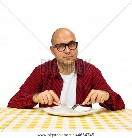 Young adult bold man sitting at the dinner table with fork and knife raised. poster