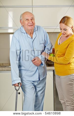 Senior man with crutches in the kitchen getting help from eldercare assistant