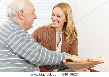 Senior citizen with smiling caregiver woman reading a newspaper