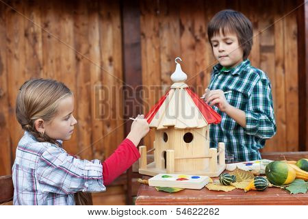 Kids painting the bird house for the winter - care for nature concept
