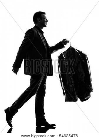 one caucasian business man holding dry clean clothes in silhouette  on white background