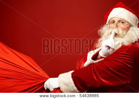 Portrait of Santa Claus with huge red sack keeping forefinger by his mouth and looking at camera poster