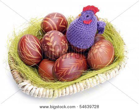 Crochet sitter sitting on easter eggs in wicker basket shot on white