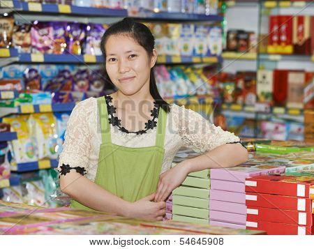 chinese young woman seller at food shop supermarket in china