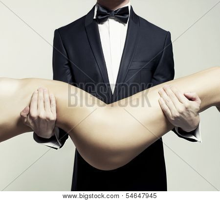 Conceptual photo. Nude lady at the hands of a man in suit