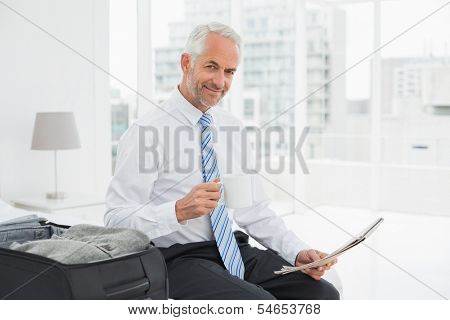 Portrait of a mature businessman with coffee cup reading newspaper by luggage at a hotel room