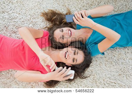 High angle view of two young female friends lying on rug and text messaging in the living room at home