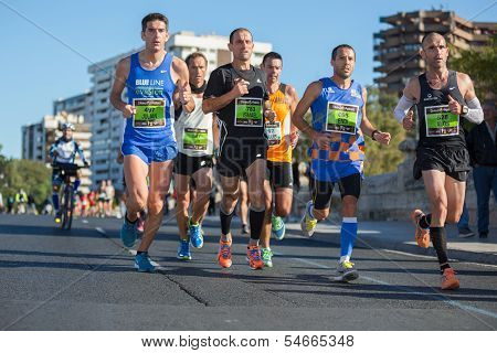 VALENCIA - NOVEMBER 17: Julian, Ismael, Endi and Alos lead their group during their participation in Valencias marathon on November 17, 2013 in Valencia, Spain poster