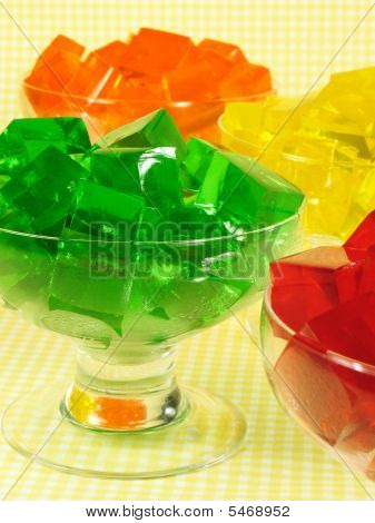 Glasses of orange green red and yellow cubed gelatin. poster
