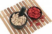Chinese herbal medicine of ginseng and wolfberry fruit. Panax schinsen, ren shen, gou qi zi. poster