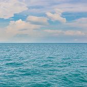 cloudy blue sky leaving for horizon above a blue surface of the sea poster